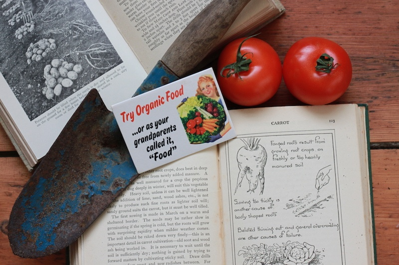 Gardening books with a shovel and tomatoes