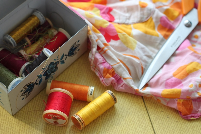 A tin of cotton reels, scissors and fabric