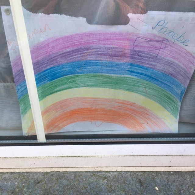 A child's drawing of a rainbow in a window