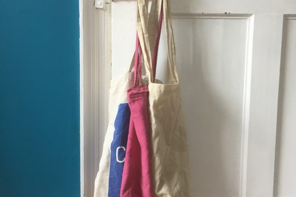Cotton reusable shopping bags hung on a door handle